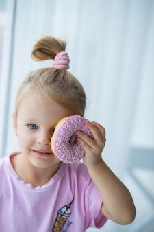 Sesja zdjęciowa dziecka z różowym pączkiem