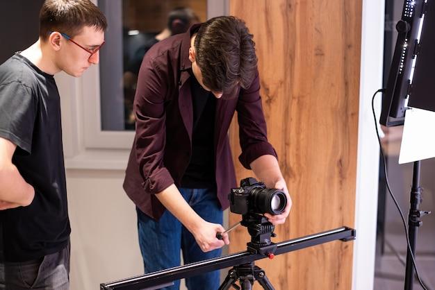 Sesja zdjęciowa w domu. dwóch fotografów, jeden trzyma aparat na poziomym pasku