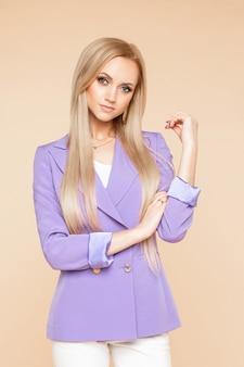 Sesja zdjęciowa w studio mody atrakcyjnej i stylowej blondynki rasy białej w klasycznej liliowej kurtce