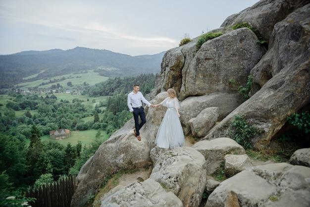Sesja zdjęciowa zakochanej pary w górach. dziewczyna jest ubrana jak panna młoda w suknię ślubną.