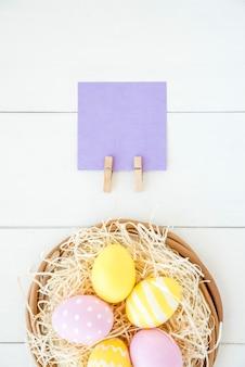 Set jaskrawi jajka w dekoracyjnym gniazdowym pobliskim papierze