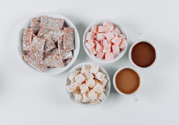 Set kawowi i tureccy zachwytów lokums w pucharach na białym tle. widok z góry.