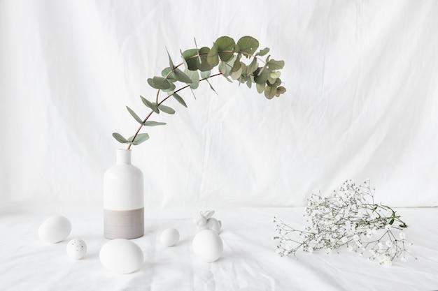 Set wielkanocni jajka blisko rośliny gałąź w wazy i kwiatu gałązkach