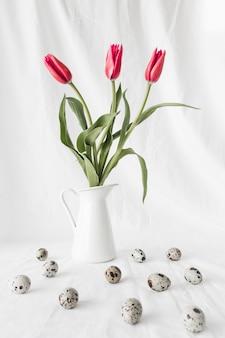 Set wielkanocni przepiórek jajka blisko kwiatów w wazie