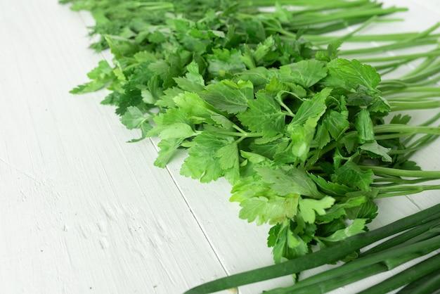 Set zielenieje dla sałatki na białym drewnianym tle. miejsce na tekst.