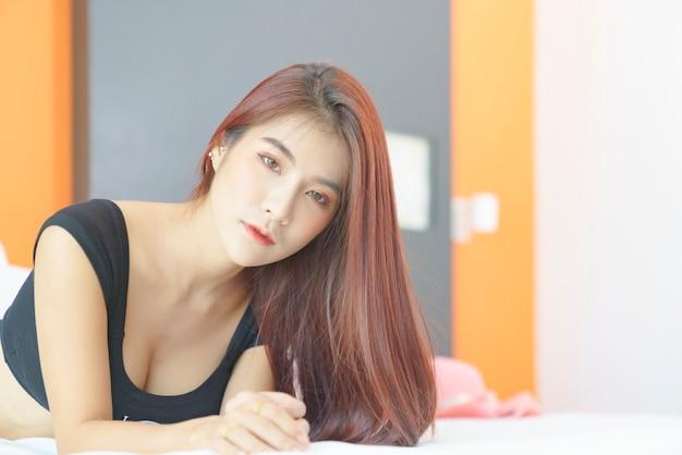 Sexy asian kobieta w czarnym bikini, leżąc na łóżku