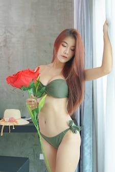 Sexy asian kobieta w zielonym bikini trzymając czerwoną różę w sypialni