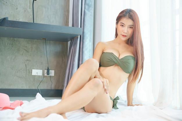Sexy asian kobieta w zielonym bikini w sypialni na wakacjach