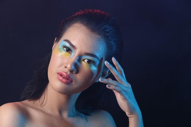 Sexy asian woman czarne włosy mokry kolor cień do powiek niebieski żółty, otwarte ramiona czerwone różowe usta, oświetlenie studyjne ciemne tło, portret pół ciała