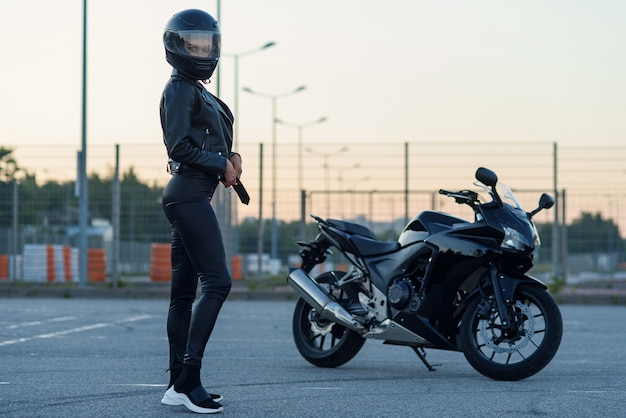 Sexy biker kobieta w czarnej skórzanej kurtce i pełnym kasku stoi w pobliżu stylowego motocykla sportowego. parking miejski, zachód słońca w dużym mieście. podróżowanie i aktywny styl życia hipsterów. siła dziewczyn.