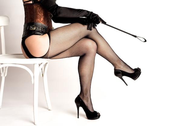 Sexy dominatrix kobieta w pończochy kabaretki gospodarstwa szpicrutą, na białym tle.