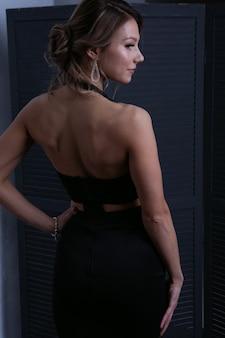 Sexy dziewczyna w czarnej sukni wieczorowej stoi przed ekranem, odwracając wzrok