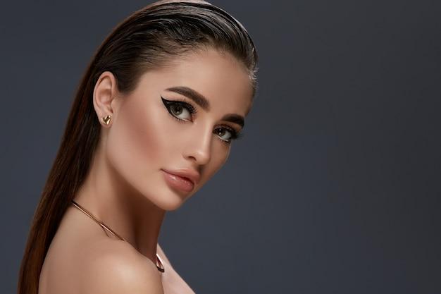 Sexy dziewczyna z czarnym makijażem i złotą biżuterią, patrząc do c
