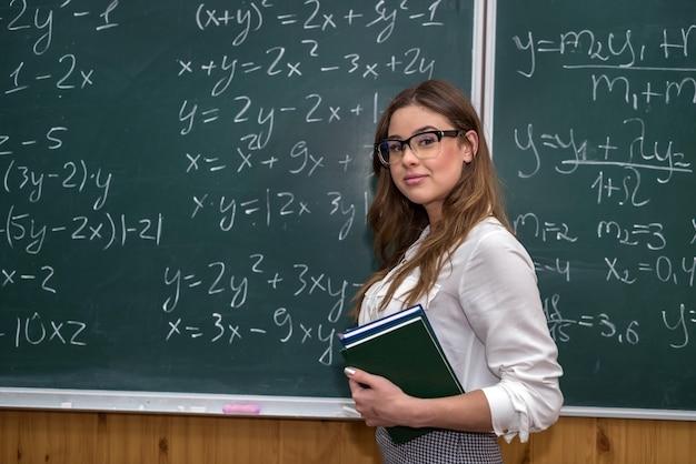 Sexy kaukaski nauczycielka przeciwko tablicy z formuł matematycznych w klasie. edukacja. szkoła