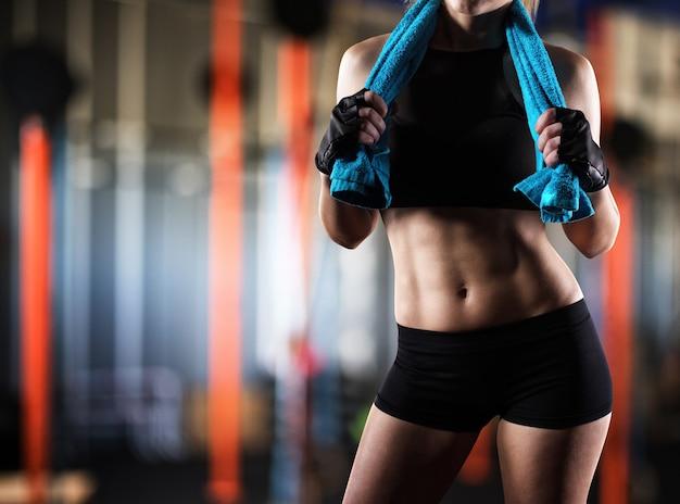 Sexy kobieta mięśni po treningu z ręcznikiem na siłowni