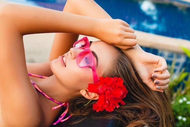 Sexy kobieta na wakacjach, leżąc przy basenie w bikini i różowe okulary przeciwsłoneczne, tropikalne kwiaty, kolorowy letni styl mody