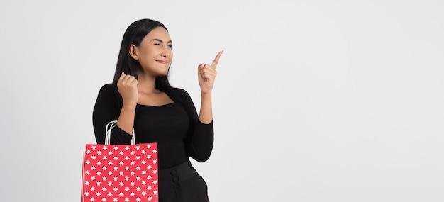 Sexy kobieta na zakupy. piękna dziewczyna ubrana w czarny gospodarstwa czerwone torby na zakupy izolowanych na białym