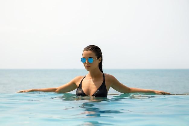 Sexy kobieta relaks w basenie podczas letnich wakacji