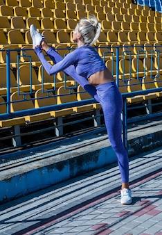 Sexy kobieta rozciągania na świeżym powietrzu. wysportowana kobieta w treningu odzieży sportowej na stadionie. rozgrzewając jej mięśnie. kobiece elastyczne ciało. joga i pilates. sport zdrowy styl życia. trener fitnessu.