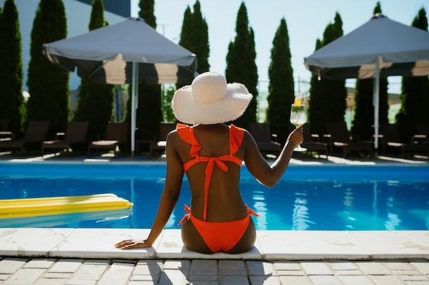 Sexy kobieta siedzi na skraju basenu, widok z tyłu. szczęśliwi ludzie bawią się na letnie wakacje, impreza świąteczna przy basenie na świeżym powietrzu. kobieta spędza czas wolny w ośrodku