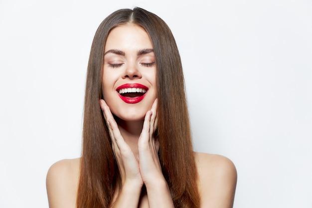 Sexy kobieta śmieje się i dotykać jego twarzy rękami czerwone usta na białym tle jasnym tle