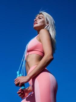 Sexy kobieta szkolenia z skakanka na tle nieba, energia.