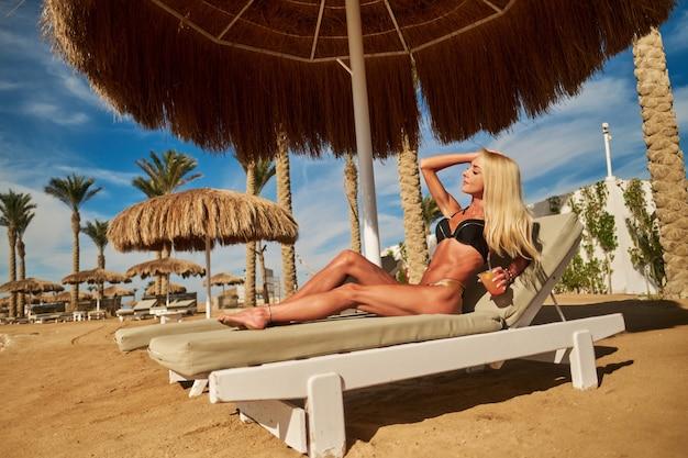 Sexy kobieta ubrana w bikini siedzi na leżaku pod parasolem baldachimu słomy na plaży trzymając szklankę przy koktajlu lub napoju