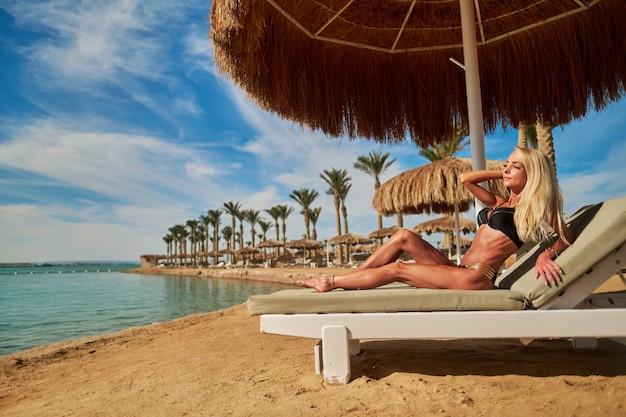 Sexy kobieta ubrana w bikini siedzi na leżaku pod parasolem baldachimu słomy na plaży