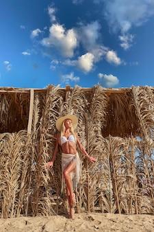 Sexy kobieta ubrana w bikini stojąc na leżaku pod baldachimem ze słomy na basenie ośrodka