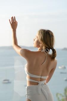 Sexy kobieta w białym bikini stojąc w pobliżu okna w willi z widokiem na ocean.