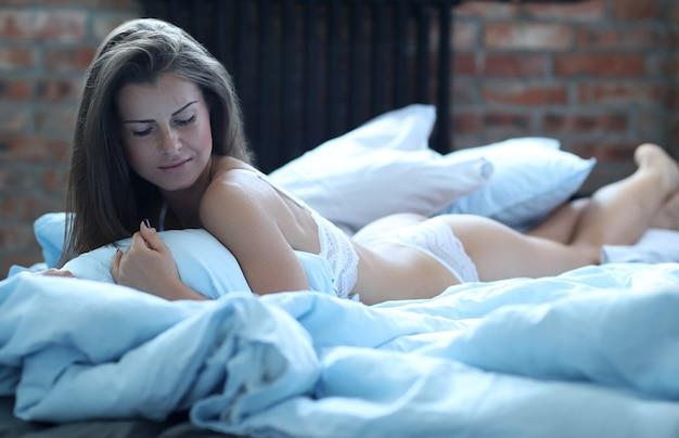Sexy kobieta w bieliźnie, leżąc na łóżku