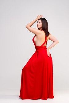 Sexy kobieta w czerwonej sukience na szarej ścianie, portret pełnej długości