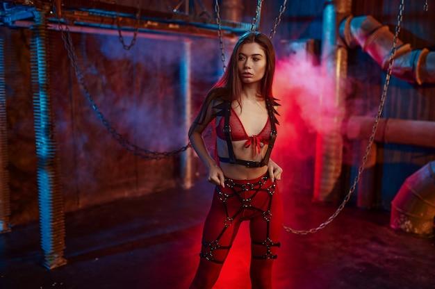 Sexy kobieta w czerwonym kostiumie bdsm przykuty łańcuchem, wnętrze opuszczonej fabryki. młoda dziewczyna w erotycznej bieliźnie, fetysz seksu, fantazje seksualne