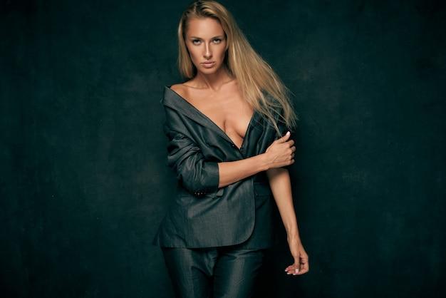 Sexy kobieta w garniturze na nagim ciele na ciemnym tle