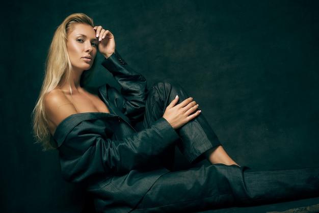 Sexy kobieta w męskim garniturze na nagim ciele długie włosy na ciemnym tle