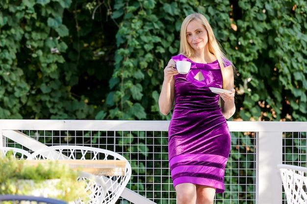 Sexy kobieta w średnim wieku ubrana w fioletową sukienkę stojącą przed liściem