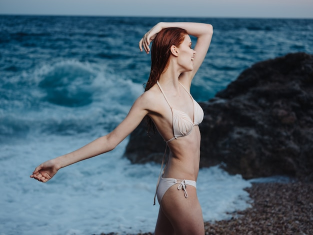 Sexy kobieta w stroju kąpielowym na plaży w pobliżu morza w przyrodzie gesty rękami.