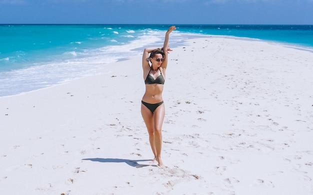 Sexy kobieta w stroju kąpielowym stojąc na piasku nad oceanem