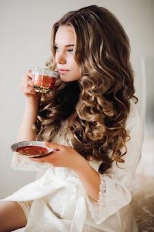 Sexy kobieta w szlafroku picia herbaty rano.
