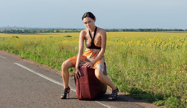 Sexy kobieta w szpilkach siedzi na dużej walizce na poboczu drogi w kraju autostopem