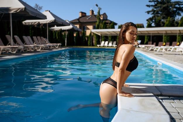 Sexy kobieta wychodzi z wody w basenie na świeżym powietrzu. piękna dziewczyna relaksuje się przy basenie w słoneczny dzień, letnie wakacje atrakcyjnej osoby płci żeńskiej