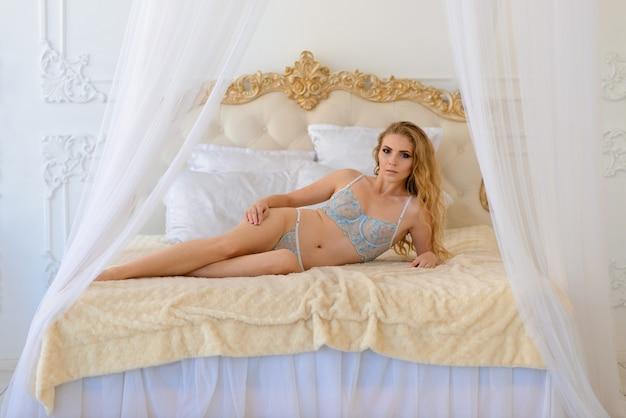 Sexy kobieta z blond falowane włosy w bieliźnie pozowanie w starodawnym wnętrzu
