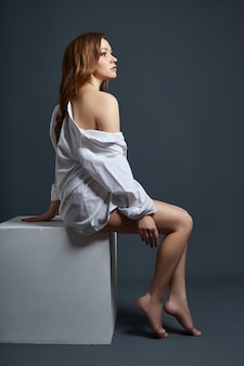 Sexy kobieta z długimi nogami i włosami, pozowanie na ciemnym tle. piękne oczy i czysta, gładka skóra