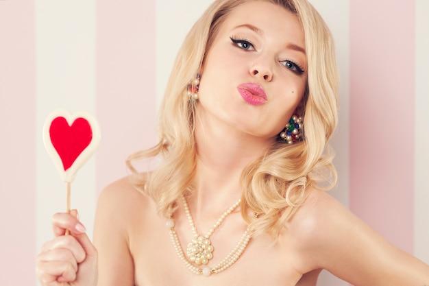 Sexy kobieta z lizakiem w kształcie serca dmuchanie pocałunkami