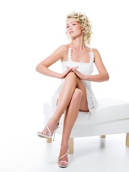 Sexy kobieta z pięknymi nogami siedzi na białym krześle