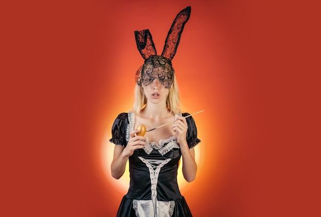 Sexy kobieta z uszami królika trzymając kolorowe pisanki, patrząc na przestrzeń kopii aparatu. wyraz twarzy. zajączek wielkanocny. piękna zmysłowa blondynka.
