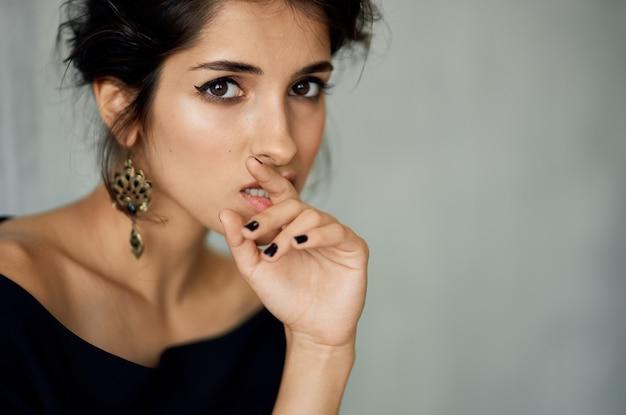 Sexy kobieta z wieczorowym makijażem i modne w kolczyki portret z bliska