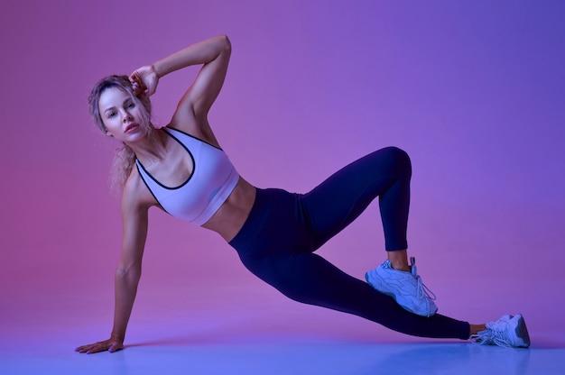 Sexy lekkoatletka, trening w studio, neonowe tło. fitness kobieta na sesji zdjęciowej, koncepcja sportu, motywacja do aktywnego stylu życia