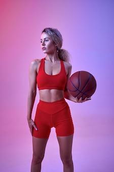 Sexy lekkoatletka w czerwonej odzieży sportowej pozuje z piłką w studio, widok z tyłu, neonowe tło. fitness sportsmenka na sesji zdjęciowej, koncepcja sportu, motywacja do aktywnego stylu życia