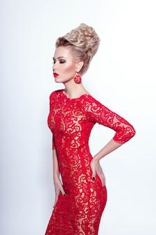 Sexy młoda kobieta z zamkniętymi oczami, w czerwonej sukience i akcesoriach, na białym tle